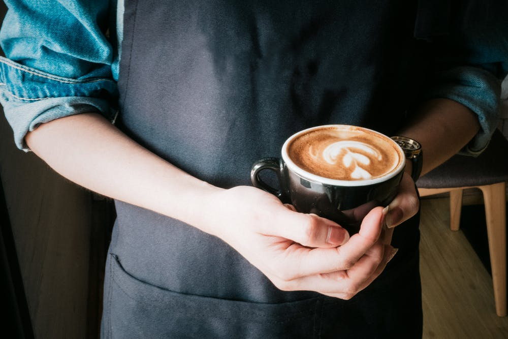 Photo of arm of barista holding a cappuccino coffee.