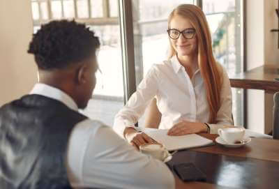 Photo of woman and man having a meeting at a desk
