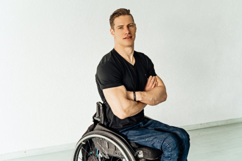Young man confident, with arms crossed, sitting in wheelchair
