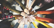 Photo of people joining hands together