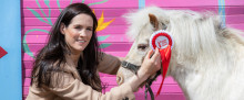 Coca Cola Thank You Fund photo of Irish jockey Rachel Blackmore with a horse with a rosette that says Thank You Fund